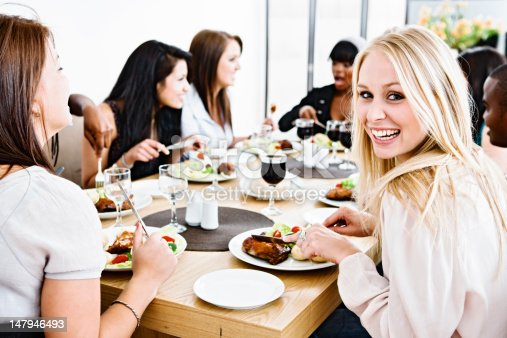 A happy group of young friends or colleagues gather round a dining table to enjoy a meal and some fun together.