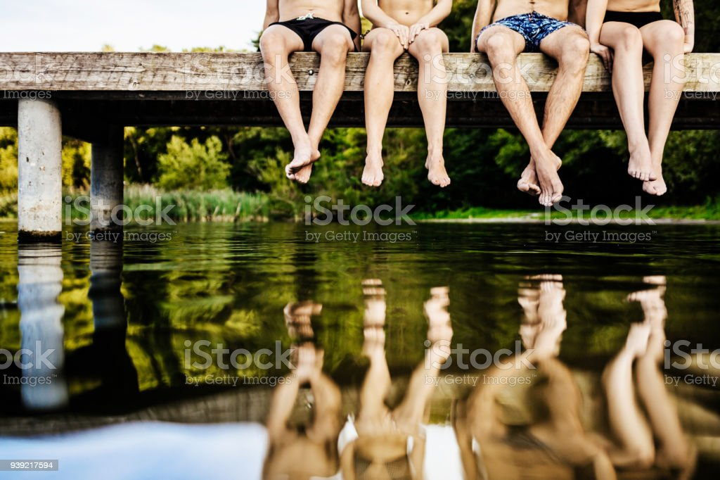Group Of Friends Legs Dangling Off Jetty stock photo