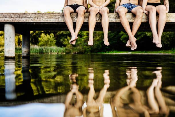 groep van vrienden poten bungelend uit jetty - schommelen bungelen stockfoto's en -beelden