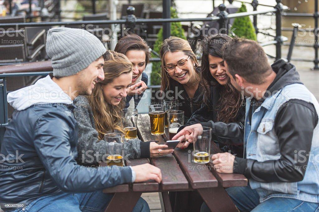 Gruppo di amici guardando uno smartphone al pub - foto stock