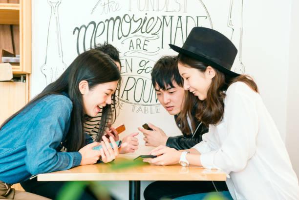 gruppe von freunden auf smartphones - ostasien stock-fotos und bilder
