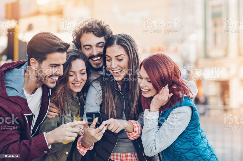 Group of friends looking at the phone and pointing stock photo