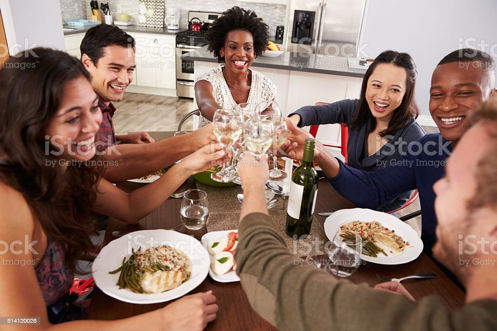 Group Of Friends Making A Toast At Dinner Party stock photo