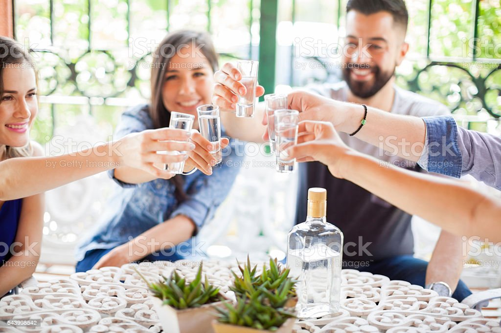 Group of friends making a toast with tequila stock photo