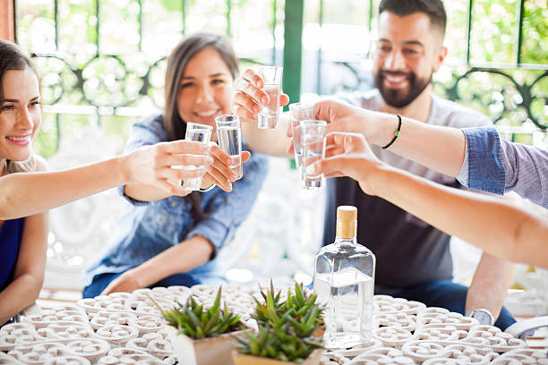 Group of friends making a toast with tequila - Photo