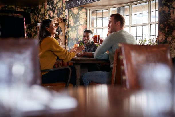 gruppe von freunden machen toast, wie sie sich für mittagsgetränke in traditionellen englischen pub - liebeskummer englisch stock-fotos und bilder
