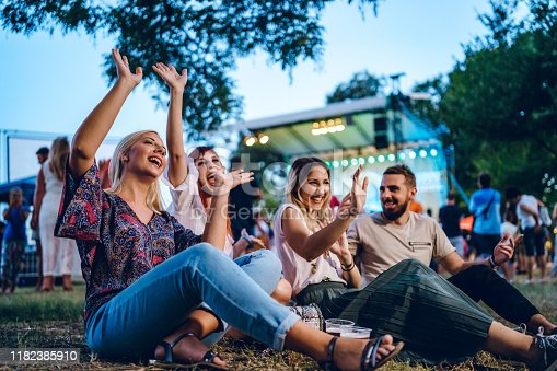 Group of young Caucasian friends on a music festival sitting in a grass together.