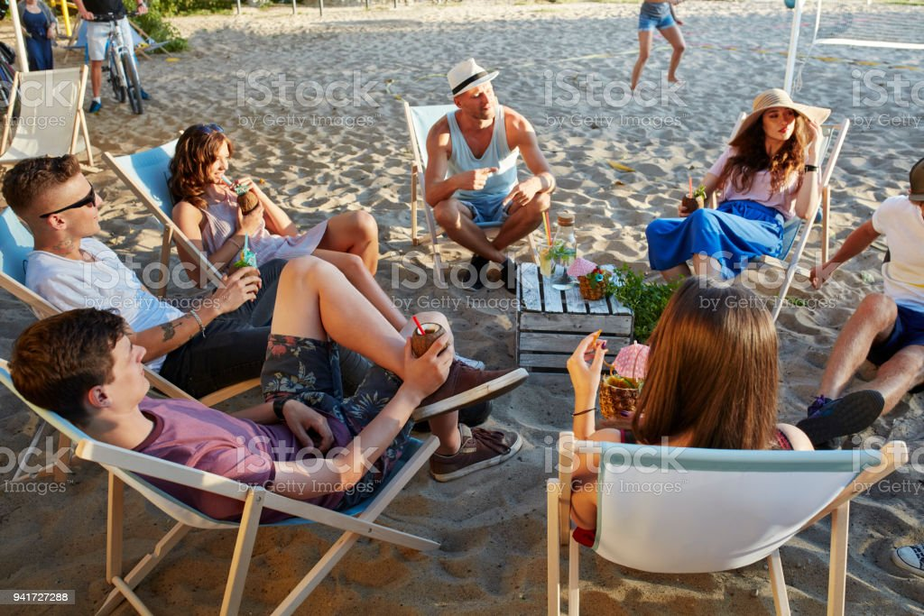 Group of friends on a picnic. Urban beach stock photo