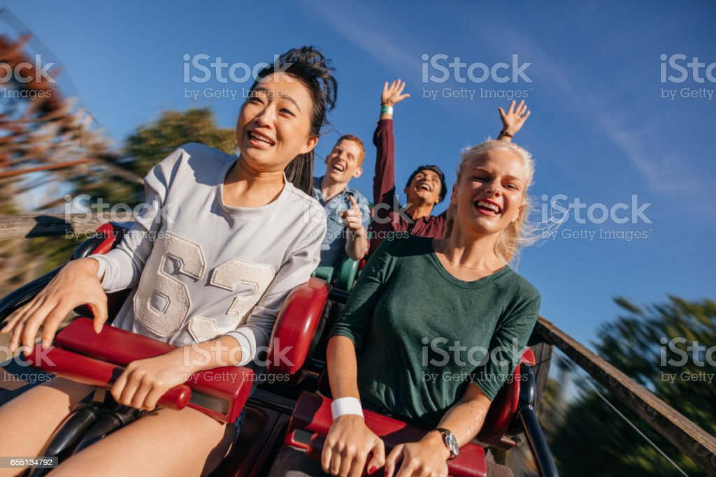 Group of friends on a thrilling roller coaster ride stock photo
