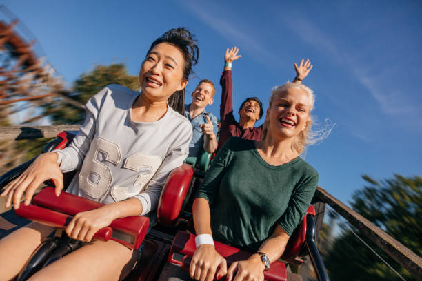 group of friends on a thrilling roller coaster ride - roller coaster stock pictures, royalty-free photos & images