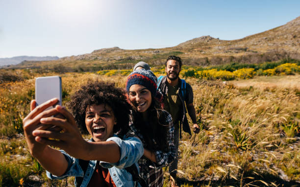 group of friends on country hike taking selfie - voyages en afrique photos et images de collection