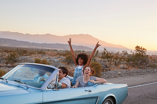 istock Group Of Friends On Road Trip Driving Classic Convertible Car 1030407908