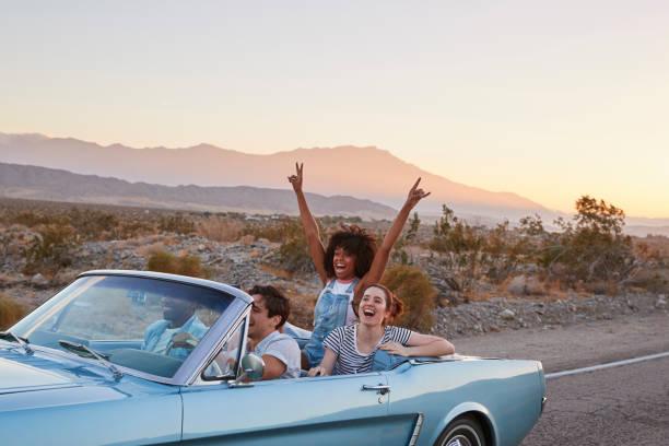 grupo de amigos en viaje por carretera conduciendo el coche descapotable clásico - viaje a estados unidos fotografías e imágenes de stock