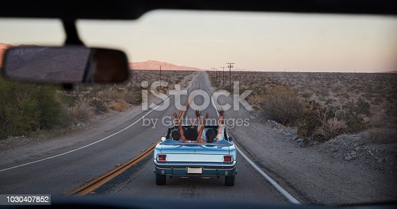 1030408008 istock photo Group Of Friends On Road Trip Driving Classic Convertible Car Viewed Through Windshield Of Following Vehicle 1030407852