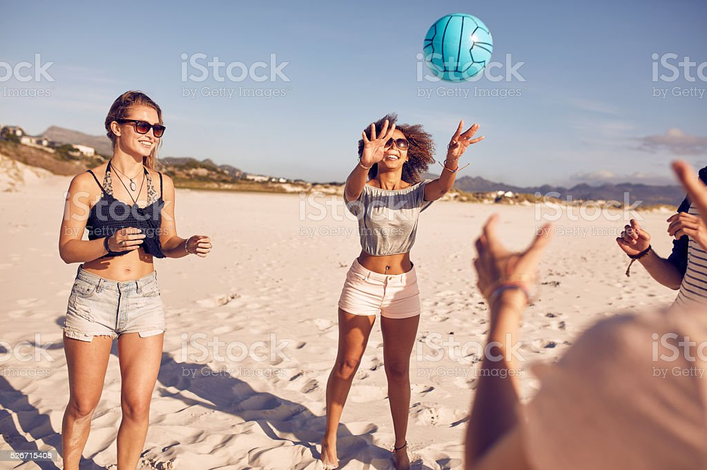 Group of friends on the beach playing volleyball stock photo