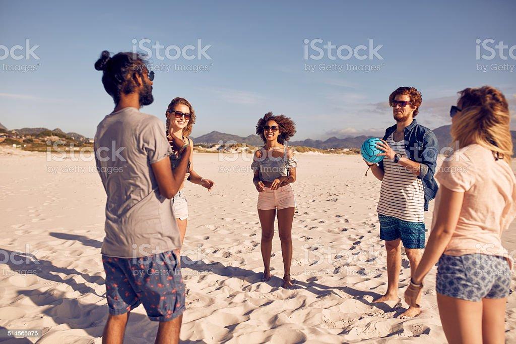 Groupe de vos amis sur la plage jouant avec ballon - Photo