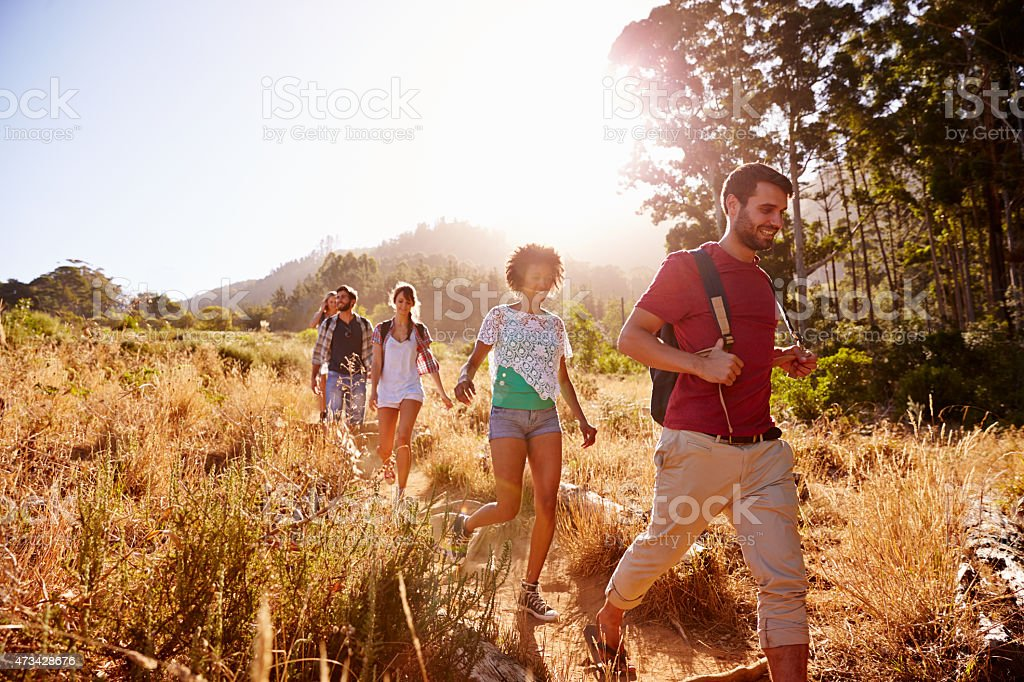 Group Of Friends On Walk Through Countryside Together stock photo