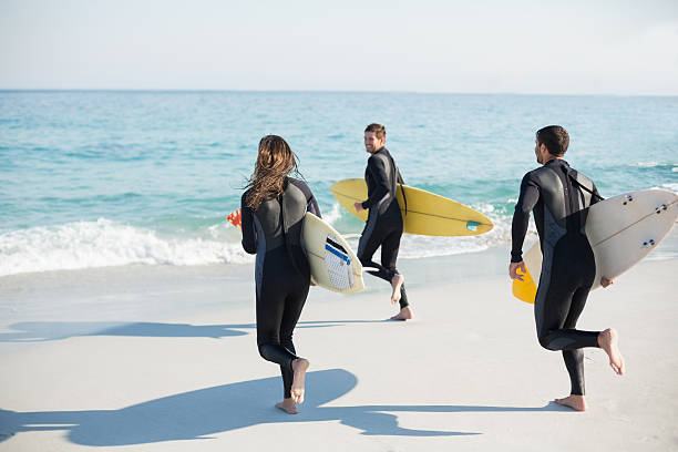 Group of friends on wetsuits with a surfboard Group of friends on wetsuits with a surfboard on a sunny day at the beach wetsuit stock pictures, royalty-free photos & images
