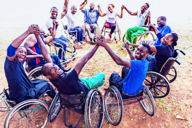 Group of Friends on Wheelchair Seated in a Circular Formation holding hands and Cheering stock photo