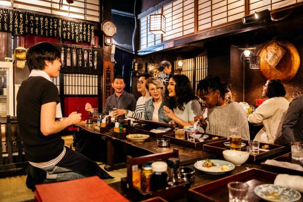 Group of friends ordering food in Japanese Izakaya stock photo