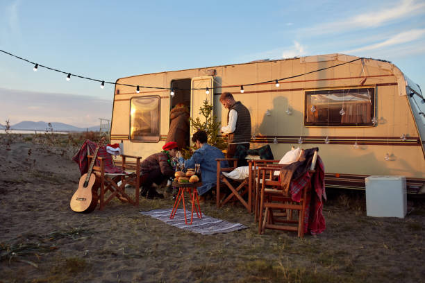 Group Of Friends Organizing New Year's Party In Front Of Their Camper Trailer stock photo