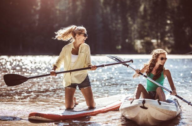 gruppe von freunden paddling (sup) auf see - stehpaddeln stock-fotos und bilder