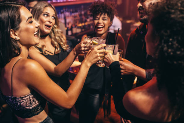 Group of friends partying in a nightclub Group of friends partying in a nightclub and toasting drinks. Happy young people with cocktails at pub. nightclub stock pictures, royalty-free photos & images