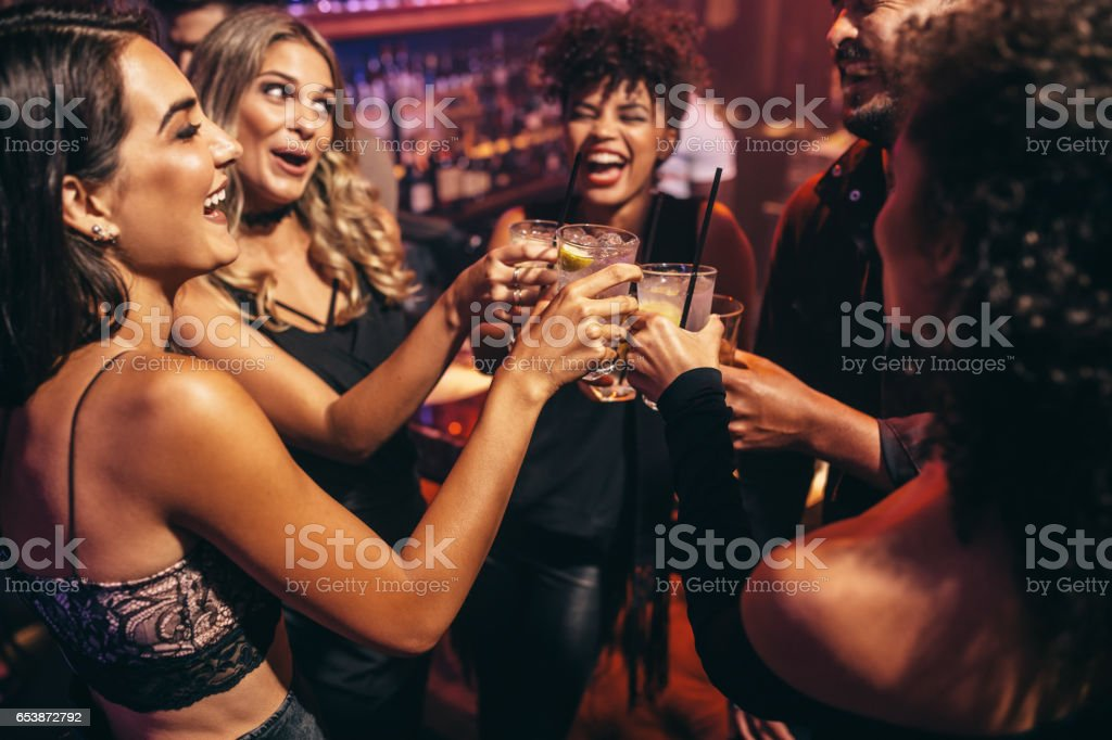 Group of friends partying in a nightclub стоковое фото