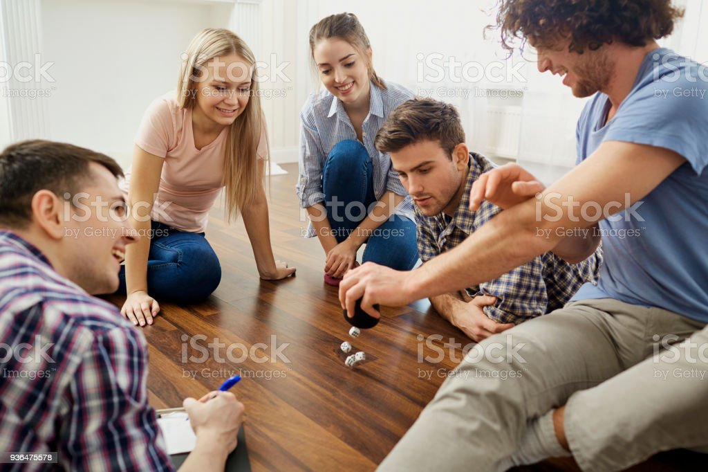 A group of friends play board games on the floor indoors stock photo