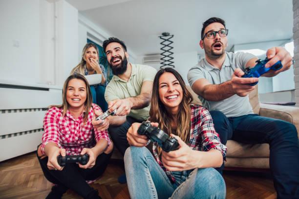 groep vrienden videospelletjes spelen samen. - gaming stockfoto's en -beelden