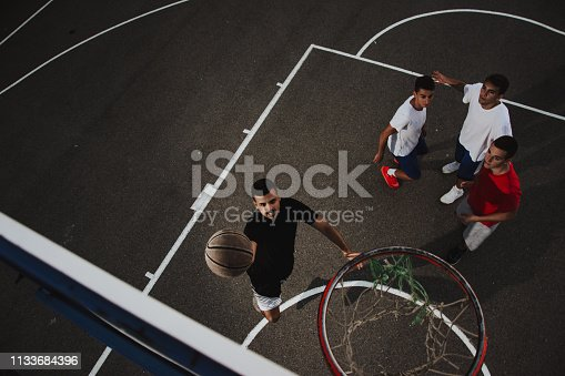 istock Group of friends playing basketball 1133684396