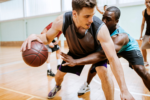 Close up for friends playing basketball at a gymnasium