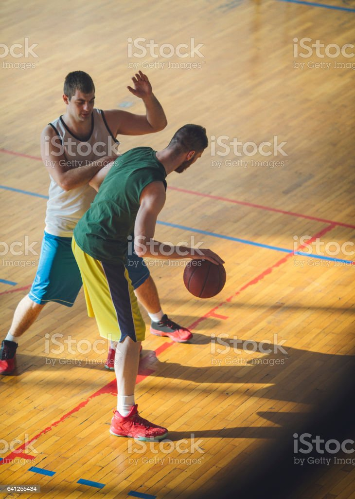 Group of friends playing basketball indoors. One player dribbling ball