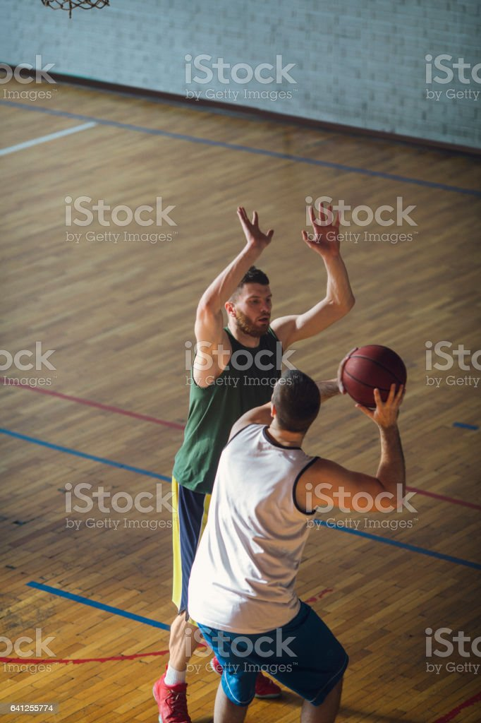 Group of friends playing basketball indoors