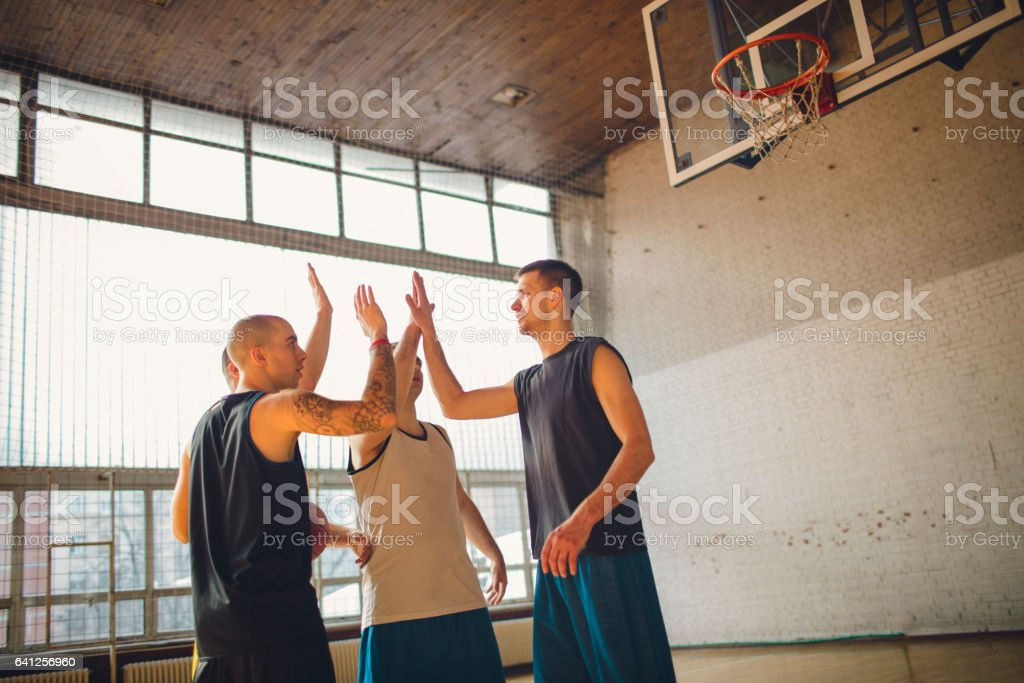 Group of friends playing basketball indoors. Giving high five after...