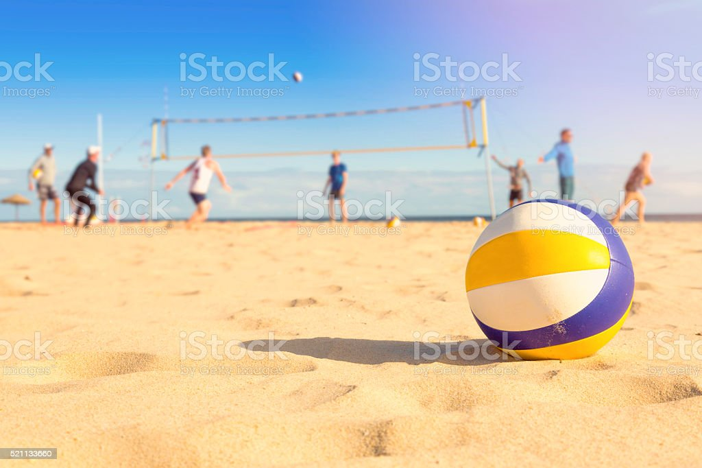 group of friends playing beach volleyball stock photo