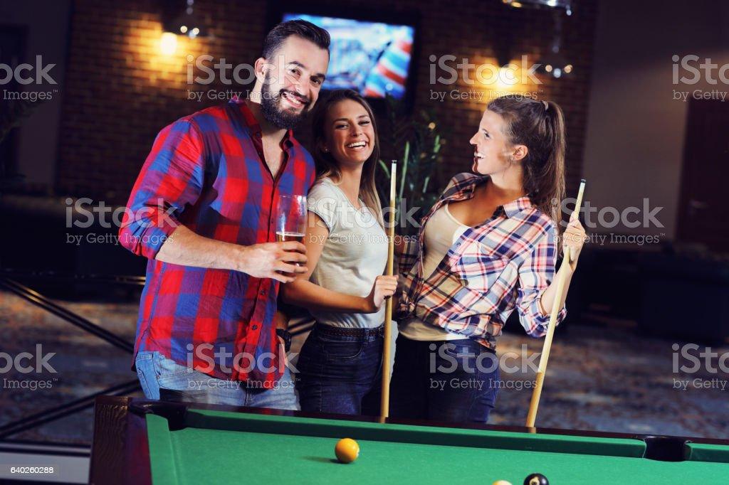Group of friends playing billards stock photo