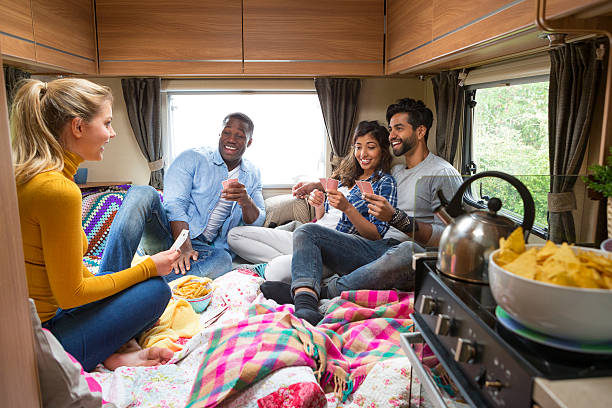 Group of Friends Playing Cards in Caravan Group of friends having fun playing cards in caravan. rv interior stock pictures, royalty-free photos & images