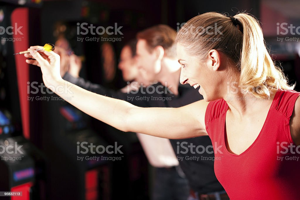 Group of friends playing darts royalty-free stock photo