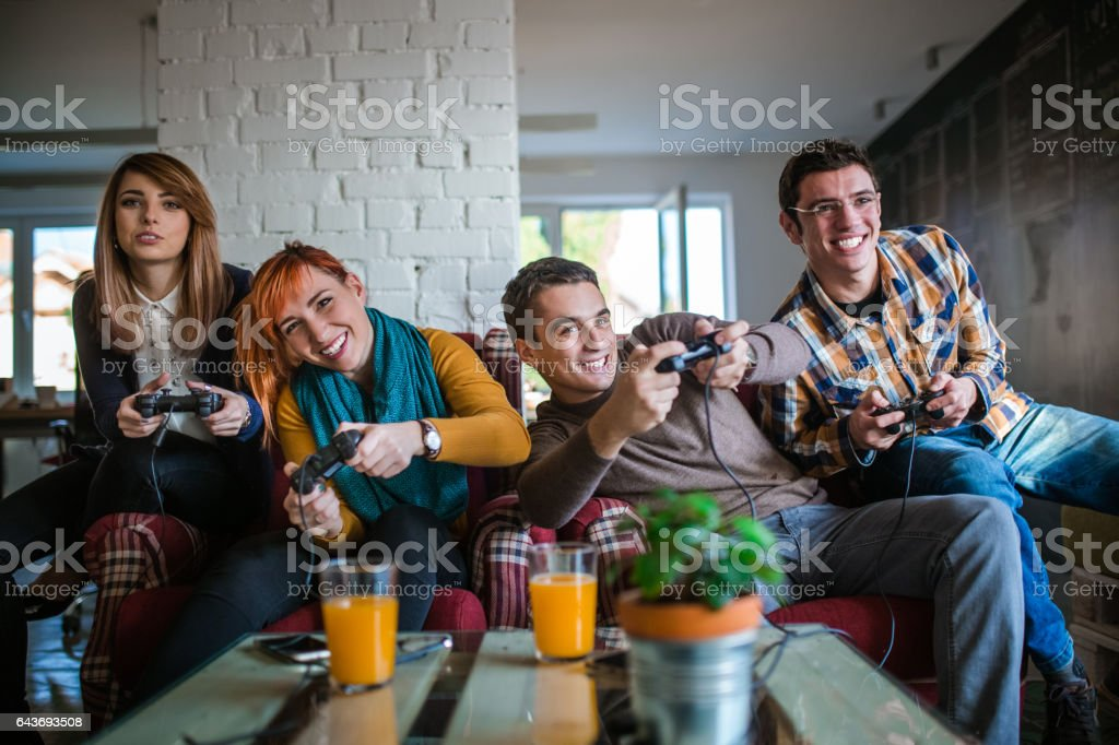 Group of friends playing digital games at home. stock photo