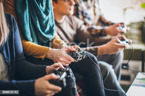 Group of young happy friends playing video games at home.