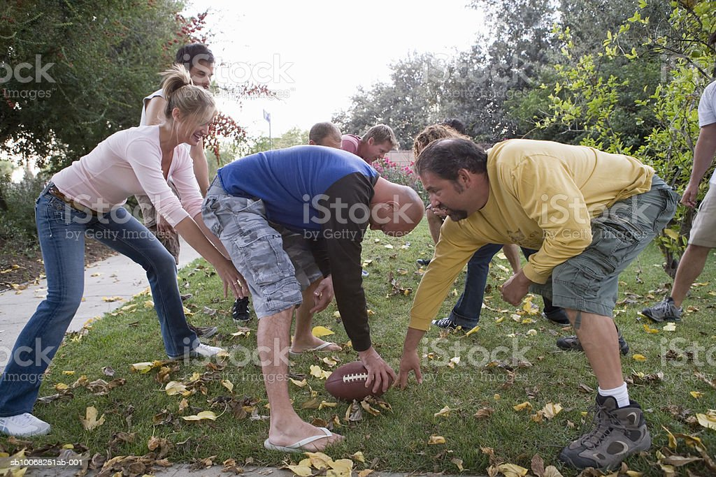Group of friends playing football in park royalty-free stock photo