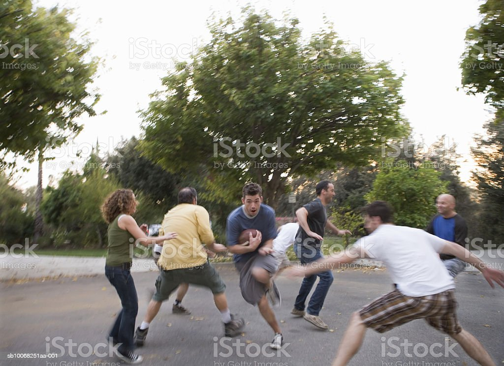 Group of friends playing football in street royalty-free stock photo