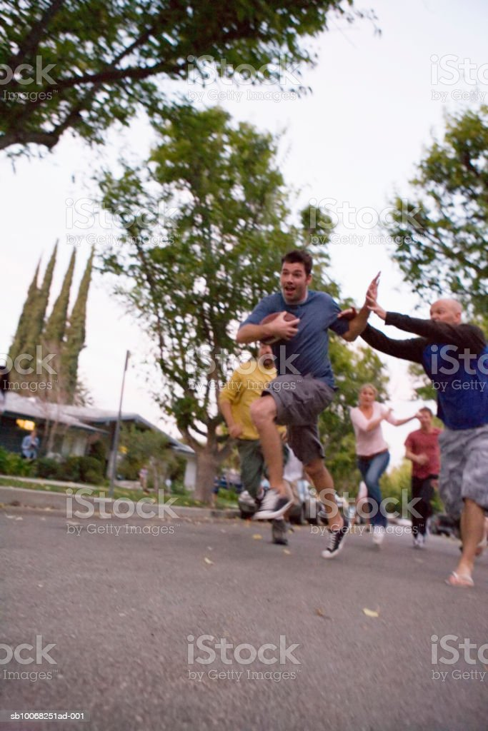 Group of friends playing football in street royalty free stockfoto