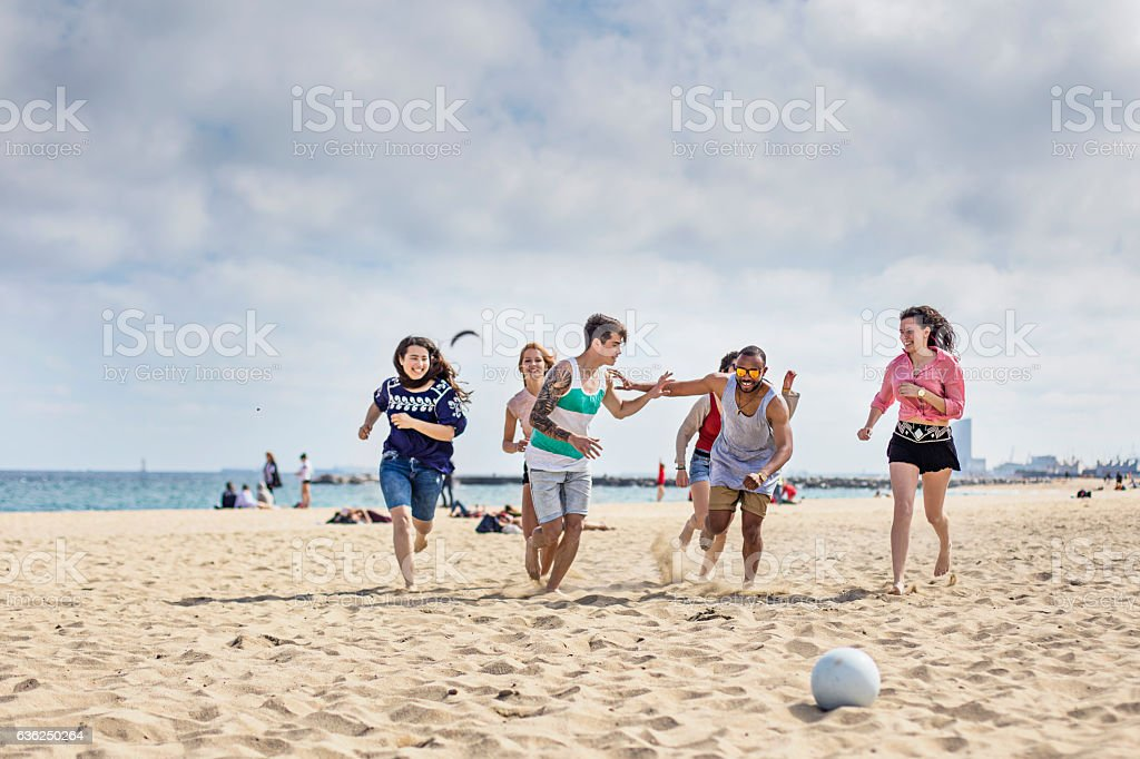 Group of friends playing football on the beach stock photo