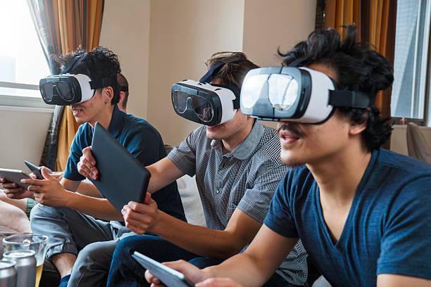 Grupo de amigos jogando jogos de realidade virtual de usar fones de ouvido - foto de acervo