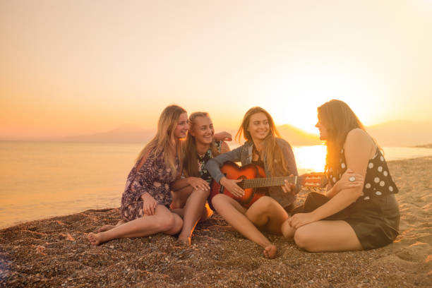 Group of friends playing guitar on the beach at sunset stock photo