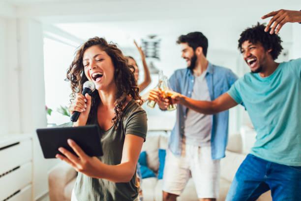 Grupo de amigos jugando karaoke en casa - foto de stock