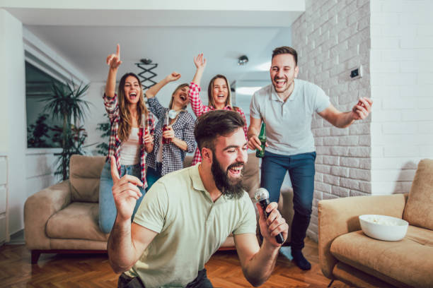 group of friends playing karaoke at home - singing stock photos and pictures