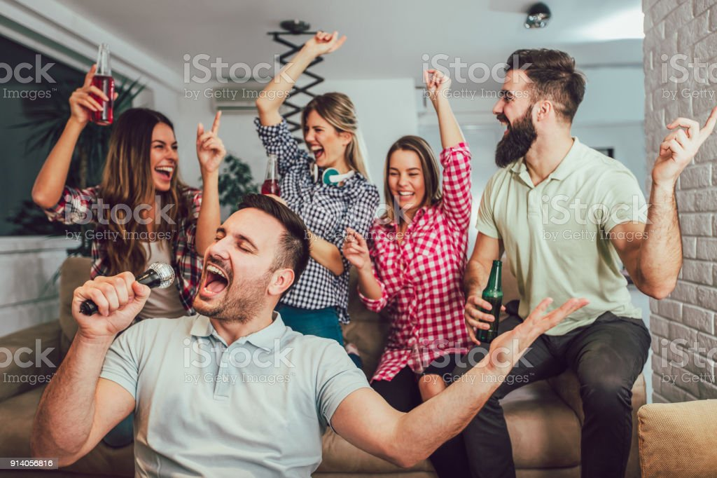 Group of friends playing karaoke at home stock photo